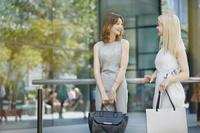 オフィス街で立ち話をする若い女性