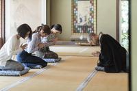 お寺でお辞儀をする住職と日本の女性