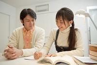 勉強する女子高校生と指導する父親