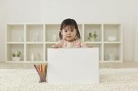 リビングで白紙のスケッチブックをを持つ女の子