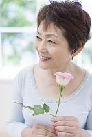 バラの花を持つ中高年日本人女性
