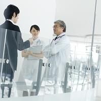 製品を売り込む製薬会社の営業マンと医者と看護師
