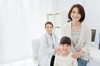 笑顔を浮かべる母娘と医者