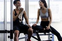 休憩するトレーニングウェアの日本人男性と女性