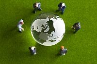 地球儀を見てミーティングをするビジネスマンのフィギュア