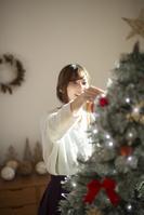 クリスマスツリーに飾り付けをする日本人女性