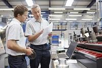 工場で働く作業員ミーティングをするエンジニアの部下と上司