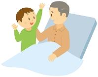 介護ベッドに座る老人男性と話しかける孫