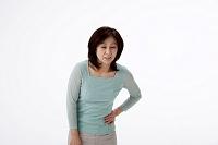 腰痛で腰に手をやる中高年女性