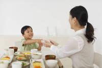 お母さんにご飯茶碗を渡す男の子