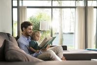 ソファで本を読む親子