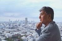 街並みを眺めるシニアの日本人男性