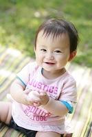公園の芝生に座る女の日本人の赤ちゃん