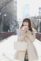 コーヒー片手に冬の街を歩く日本人女性