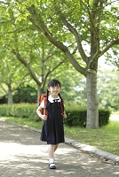 新緑の道をランドセルを背負い歩く日本人の女の子