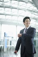 空港で時計を見るビジネスマン