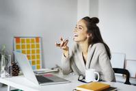 デスクでスマートフォンを利用する外国人ビジネス女性