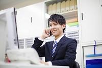 デスクで電話をする日本人ビジネスマン