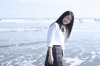 砂浜で水遊びする女子高生