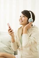 スマホで音楽を聴く笑顔の20代女性