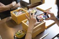 料理の写真を取る日本人のシニア女性