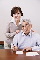 年賀状を書くシニアの日本人夫婦
