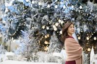 クリスマスデコレーションの屋外を歩く女性