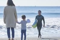 サーフィンをする父親と見守る日本人家族