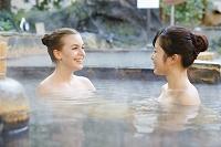 温泉に浸かる外国人と日本人の女性