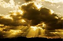 雲の切れ間から射すあかね色の光