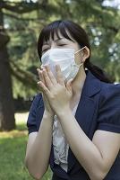 マスクをしてクシャミをする若い女性