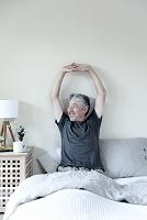 ベッドで伸びをするミドル男性