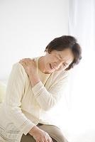 肩を押さえる年配の女性