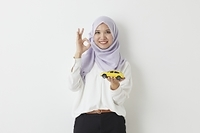 ミニカーを持つムスリムの女性