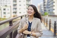徒歩で通勤する日本人ビジネスウーマン