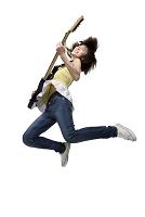 エレキギターを弾きながらジャンプする女性