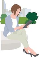 公園でタブレットを操作する若い女性