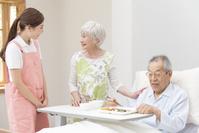 食事を手伝う介護士女性と日本人シニア夫婦