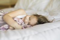 ベッドルームで毛布を抱いて寝る子供