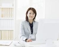 パソコンの前に座り微笑むビジネスウーマン