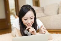 寝転がってノートパソコンを見る日本人女性