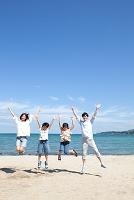 海辺でジャンプする日本人家族