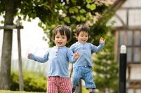 新緑の公園で遊ぶ双子の男の子