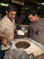 タンドールでナンを焼くインド人