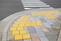 石畳に埋め込まれた点字ブロックと横断歩道