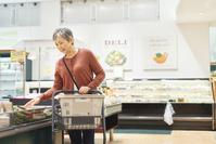 スーパーで買い物をするシニアの日本人女性