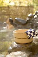桶と手ぬぐいと紅葉と露天風呂の日本人女性