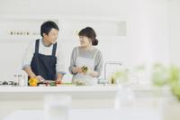 キッチンに並んで料理する日本人の若い夫婦