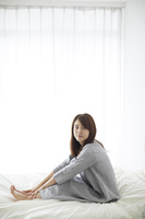 ベッドの上でストレッチをする日本人女性