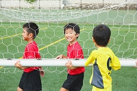 サッカーのゴールを運ぶ少年たち